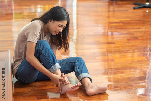 Photo injured woman with ankle pain or foot injury; portrait of asian woman falling, h