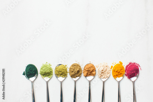 Fototapeta Kitchenware with different colorful superfood powders on wooden table obraz