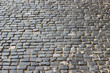 An old stoneblock pavement cobbled with rectangular natural stone blocks. Photo in perspective with selective focus