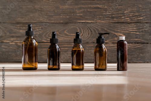 Cosmetic dark amber glass bottles on wooden background Fototapet