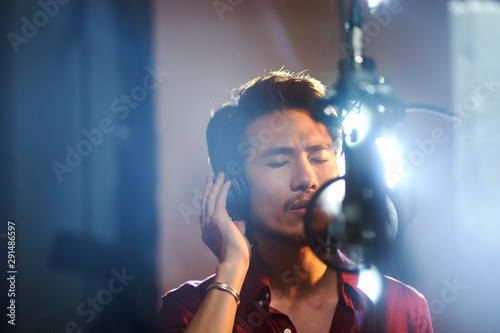 Fotografía young asian musician recording songs in studio