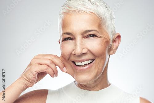 Gorgeous smiling Caucasian senior woman with short gray hair pinching her cheek Tablou Canvas