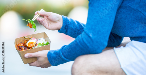 Photo Young mans hands holding lunch in a box of recycled paper