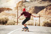 Hipster Rides On Long Board By Mountain Road
