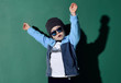 Portrait of cool kid boy in blue sunglasses, hat, fleece jacket and white t-shirt having fun jumping dancing on green