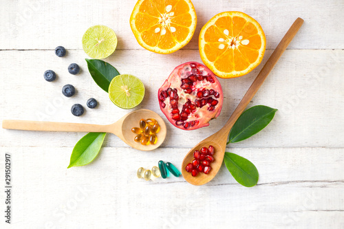 Obraz na płótnie Multivitamin supplements on wooden spoon with healthy fruit blueberry, lime, orange, pomegranete on white wooden background
