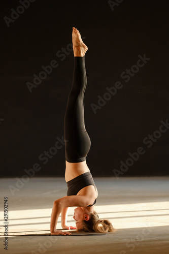 Valokuvatapetti Young sporty woman practicing yoga, doing headstand exercise, salamba sirsasana pose, working out, wearing sportswear, grey pants and top, indoor full length, yoga studio, rear view