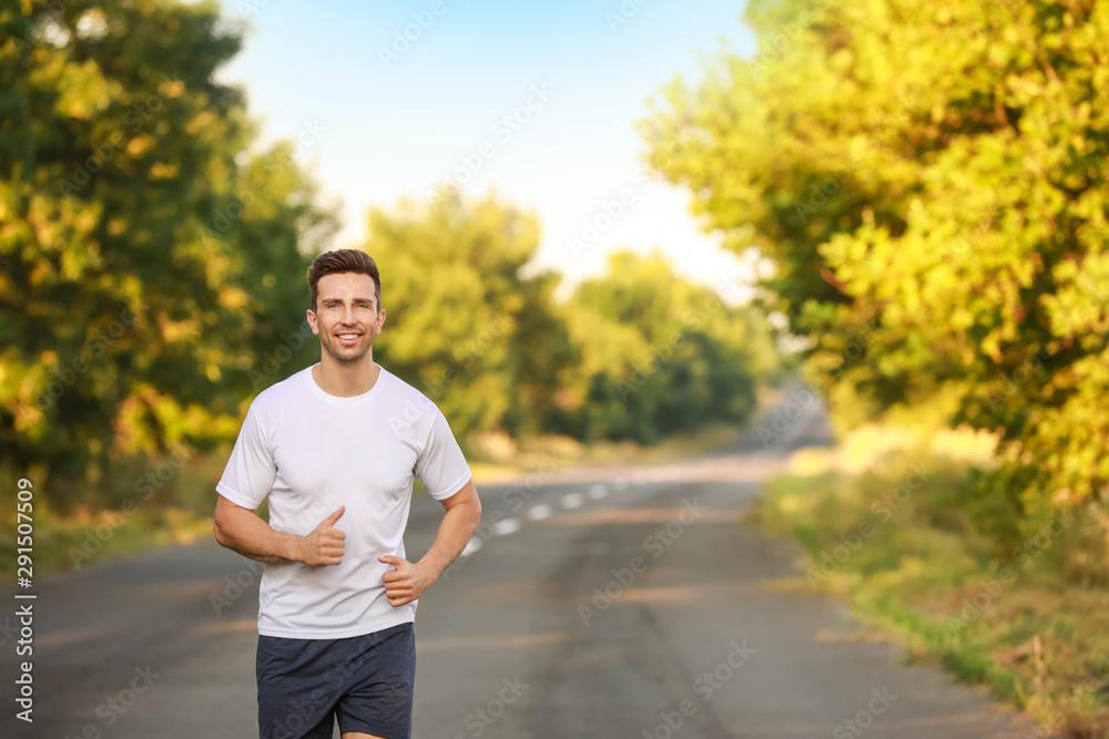 Fototapeta Sporty young man running outdoors
