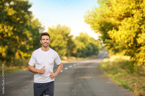 Sporty young man running outdoors - 291507509