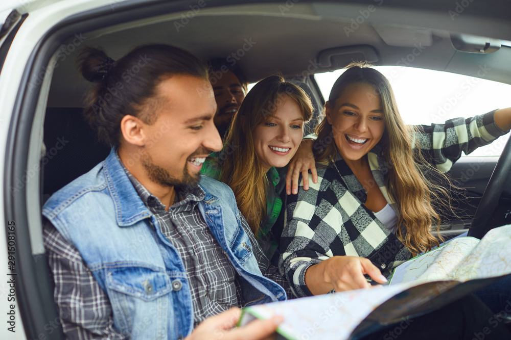 Fototapety, obrazy: A group of friends choose the route on the map ride in the car.