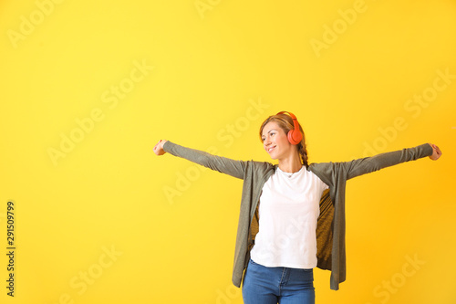 Pinturas sobre lienzo  Beautiful young woman listening to music on color background