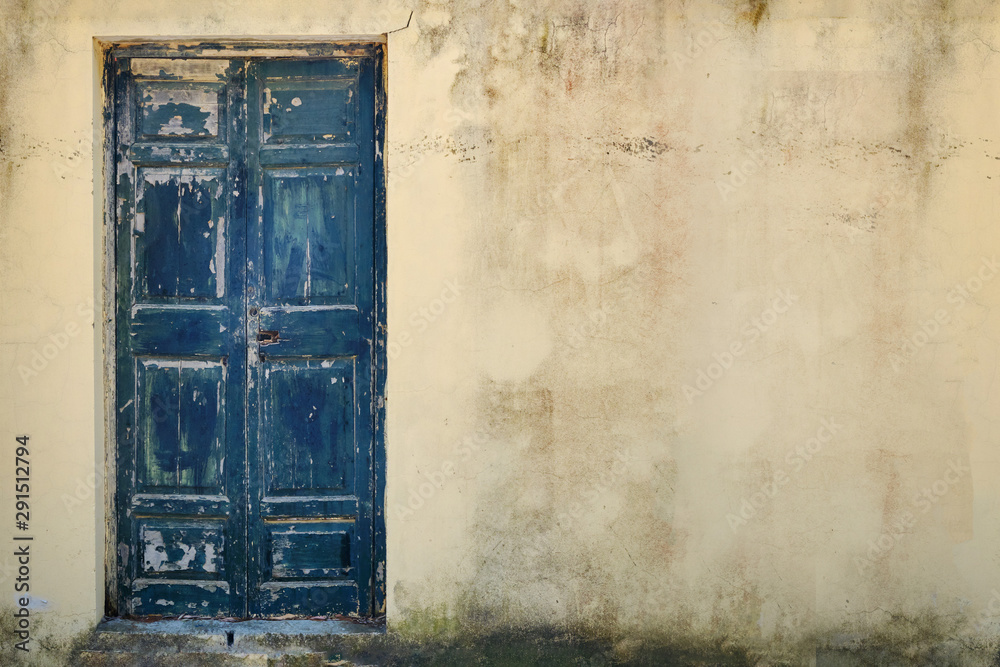 Fototapety, obrazy: Old wooden door in cracked stone wall, copy space. The background is a battered cement wall with the texture of peeling paint