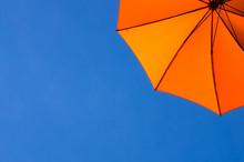 Orange Umbrella / Parasol Viewed From Below Against A Blue Sky