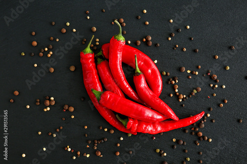 Poster Hot chili peppers Hot chili peppers and peppercorn on dark background