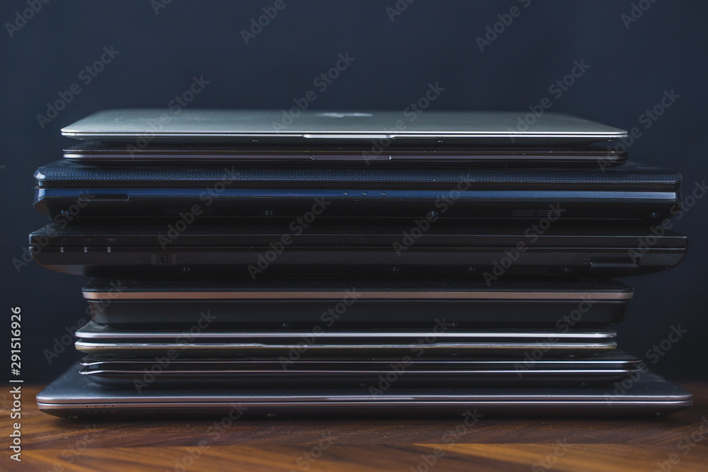 Fototapety, obrazy: Stack of old laptops with dark background. Front