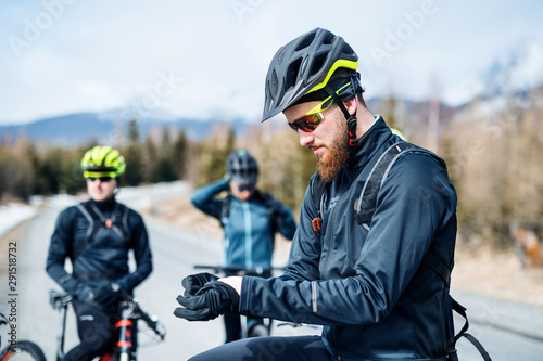 Group of mountain bikers standing on road outdoors in winter. - 291518732
