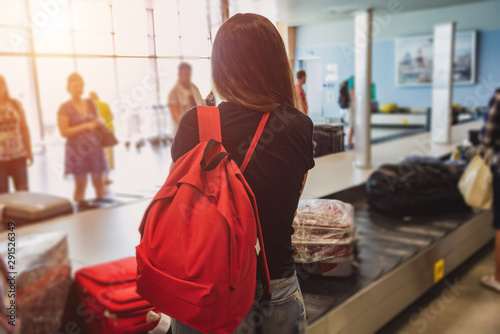 Fototapeta  A girl with a red backpack is waiting for her luggage at the airport