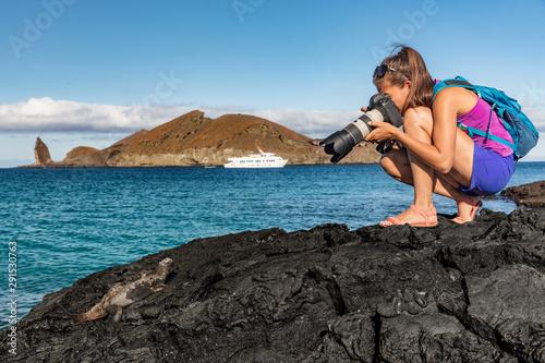 Obraz Galapagos tourist photographing marine iguana on Santiago Island in Galapagos Islands. Cruise ship and Pinnacle Rock and Bartolome Island in background. Famous Galapagos cruise ship tour destination. - fototapety do salonu