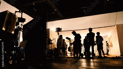 Behind the shooting video production and lighting set for filming which movie crew team working and silhouette shadow of camera and professional equipment in big studio for commercial advertising Poster Mural XXL