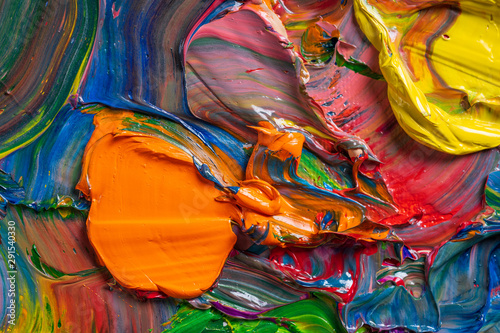 Different bright colors of oil paints are mixed on a palette close-up. - 291540330