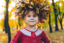 Little Toddler Girl Playing With Maple Leaves Wreath
