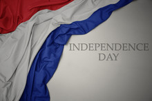 Waving Colorful National Flag Of Netherlands On A Gray Background With Text Independence Day.