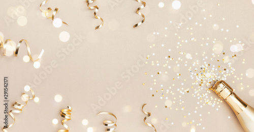 Champagne bottle with confetti stars, bokeh decoration and party streamers on golden background. Christmas, birthday or wedding concept. Flat lay. - 291542171