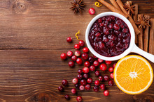 Cranberry Sauce In Ceramic Saucepan With Ingredients For Cooking On Kitchen Wooden Table Top View.
