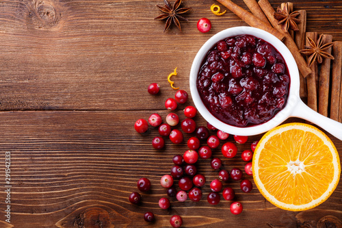 Cranberry sauce in ceramic saucepan with ingredients for cooking on kitchen wooden table top view Canvas Print
