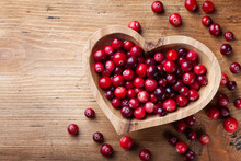 Cranberry In Wooden Bowl On Rustic Table Top View.