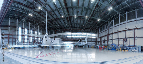 Fototapeta Passenger jet planes under maintenance. Checking mechanical systems for flight operations. Panorama of aircrafts in the hangar obraz