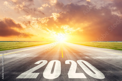Fotografía Road asphalt road with the inscription 2020 year with the rising sun in the morning