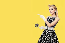 Smiling Blond Woman In Pin Up Style In Black And White Dress In Polka Dot, Showing Something Or Empty Copy Space Area For Some Text, Slogan Or Advertising, Isolated Over Yellow Color