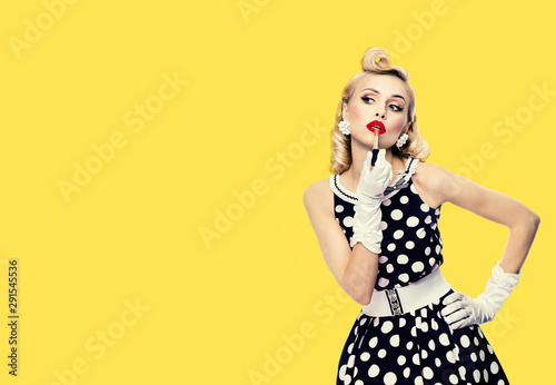 Photo Young woman in pin up style black and white dress in polka dot, applying lipstic