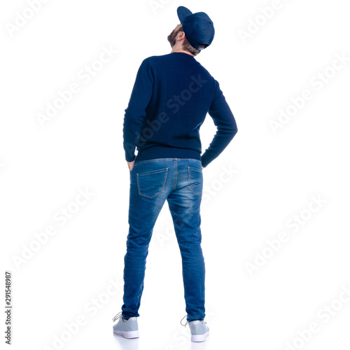 Fototapeta Man in jeans shorts, cap, casual clothing standing looking up on white background isolation, rear view obraz