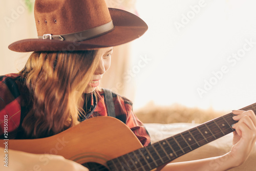 Music Concepts. Asian Caucasian girl in countryside playing guitar. Asian women relaxing with music. Asian women have a happy lifestyle. - 291550315