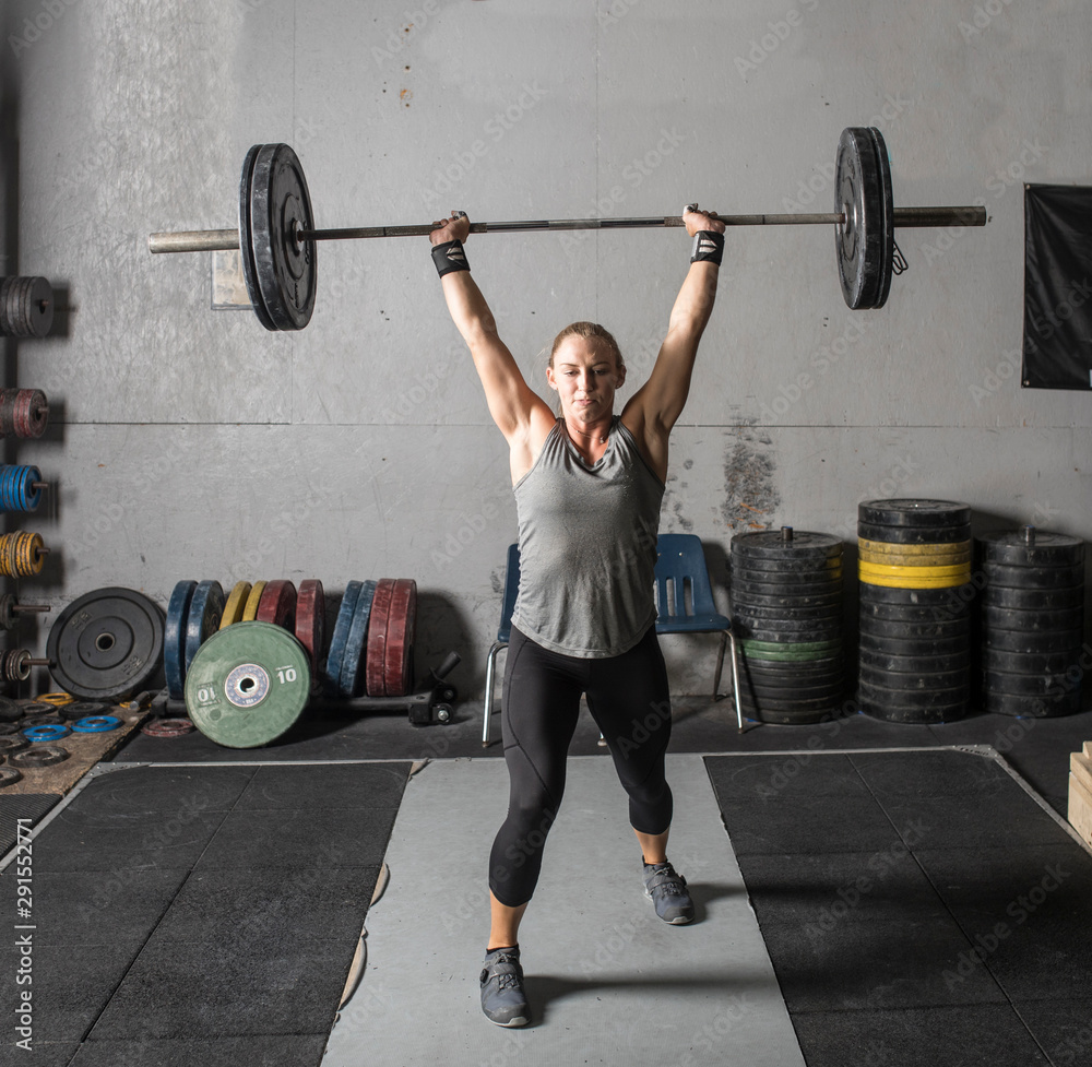 Fototapety, obrazy: Strong young woman lifting heavy barbell over her head in gym.