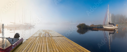Fotomural  Panorama, autumnal mist on a river with yachts and boats anchored in harbor,  at