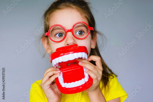 Little funny girl kid with toothbrush, dental mockup (jaw), red glasses in hand. Concept of health, oral hygiene, people and beauty. Space for your text. Selective focus.