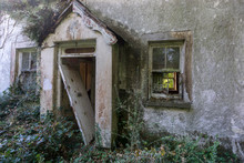 Front Of Derelict Cottage With Entrance Door Leaning To One Side In Small Porch. With A Broken Window On Either Side. Vegetation On Front Of Cottage.