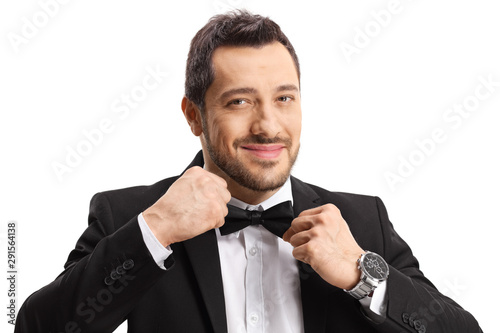 Handsome man in a suit making his bow-tie - 291564138