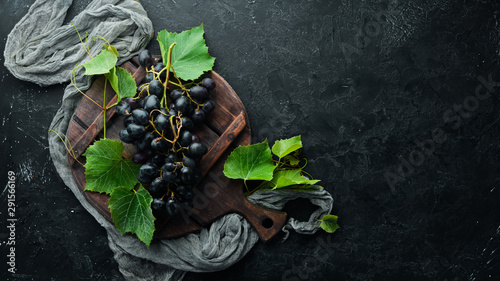 Photo  Fresh red grapes with leaves on a black stone table