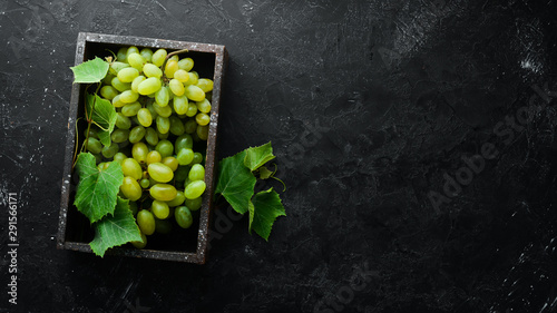 Fresh green grapes with leaves on a black stone table Wallpaper Mural