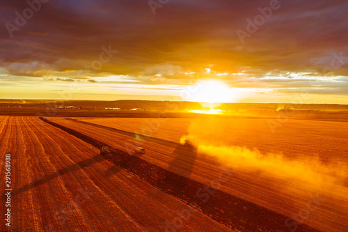 Foto auf Leinwand Rotglühen Combine harvester harvests wheat in the field at sunset in autumn in Russia. view from a height of equipment and field.