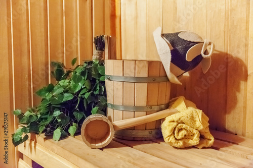 Fotomural Interior details Finnish sauna steam room with traditional sauna accessories basin birch broom scoop felt hat towel