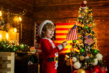 Cute Baby Toddler Celebrate Christmas. American Child Cheerful Mood Waving Flag. Kid Play American Flag Christmas Tree. Little Boy Santa Hat And Costume Having Fun. American Traditions Concept