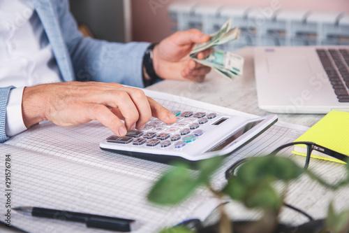 Fototapeta man hand money with calculator obraz na płótnie
