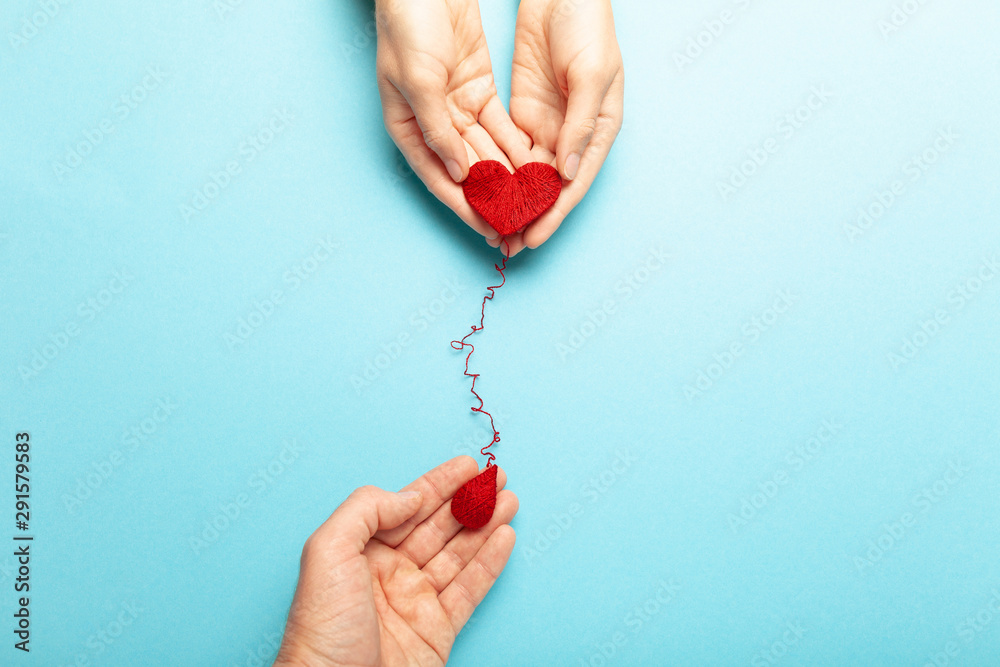 Fototapeta Blood donor. Hands with red heart and drop. Medical donation and blood transfusion.
