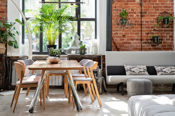 Industrial bright interior of living room in loft apartment in modern style. Bricky wall, big window and wooden table in scandinavian style.