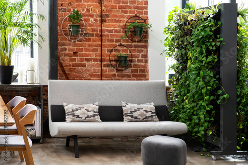 Modern interior of living room with red bricky wall and green vertical garden in loft apartment Fototapeta